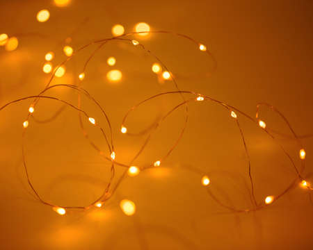 Christmas lights on yellow gold background with copy space. Decorative garland.