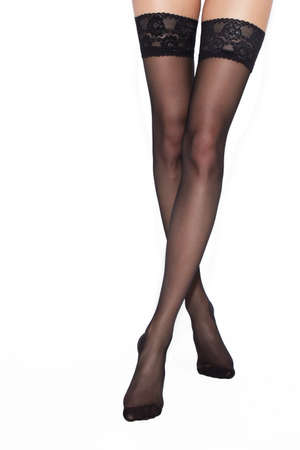 Legs of sexy young caucasian woman in black nylon tights on white background