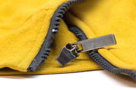 Broken zipper on yellow shirt jacket. Detail close-up photo