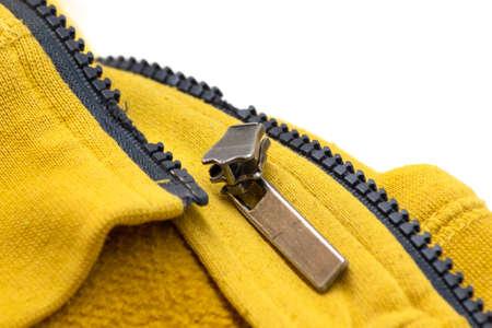 Broken zipper on yellow shirt jacket. Detail close-up photo