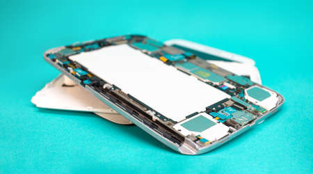 Tablet repair. Close-up disassembled mobile phone parts. Colorful blue background.