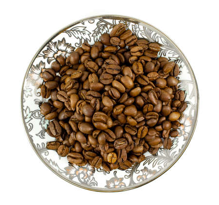 Brown coffee beans on plate with oriental pattern. Top view flat lay. Isolated on white background.