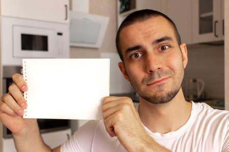 Young man holding and show blank paper notepad with space for text. Kitchen background blurred.
