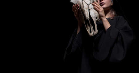 Witch holding animal cow skull skull standing on isolated black background. Halloween, black magic concept mockup.