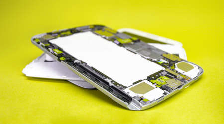 Close-up disassembled mobile phone parts. Tablet repair. Colorful yellow background. Stockfoto
