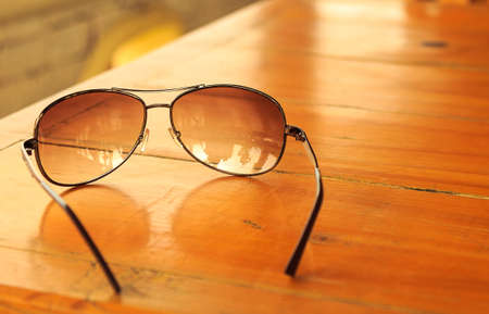 mirrored: Light brown mirrored sunglasses on the wooden table Stock Photo