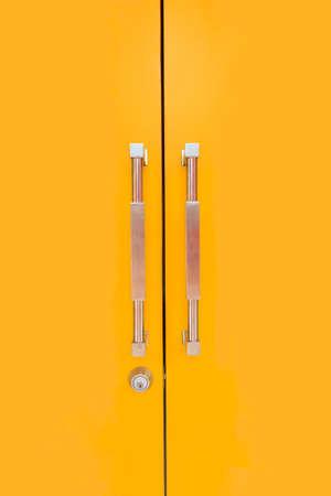 secured door: Yellow door and glossy handles with security lock Stock Photo