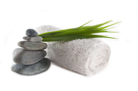 towel and stack of rocks with bamboo leaves