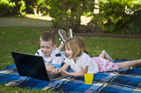 Children lying on a blanket with a laptop having fun  Stock Photo