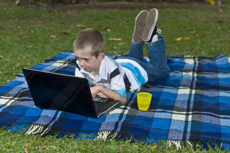 Young boy lying down on blanket with laptop Stock Photo