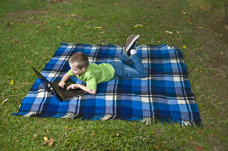 young child using  laptop lying on a blanket in the garden