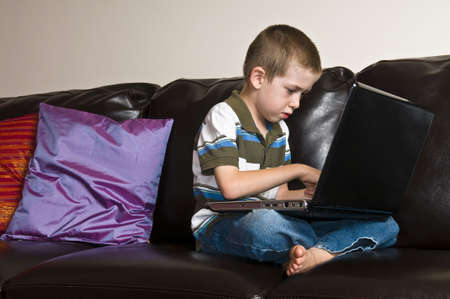 Home interior shot of a child sitting and using a laptop  Stock Photo