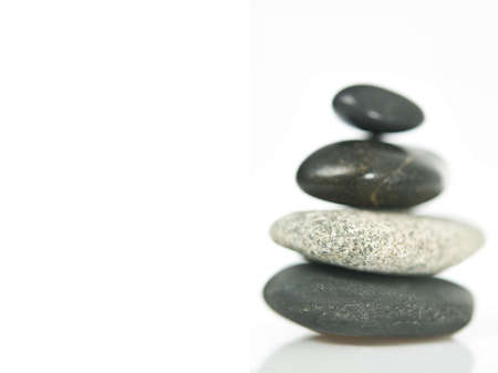 A stack of four stones with a shallow depth of feild, the stones are isolated on white.