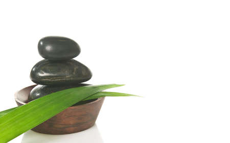 Three pebbles in a bowl with bamboo leaves, isolated on white.