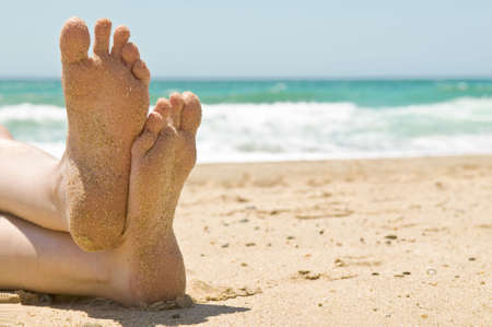 Close up of sandy feet relaxing on a beautiful beach, with waves breaking in the background.