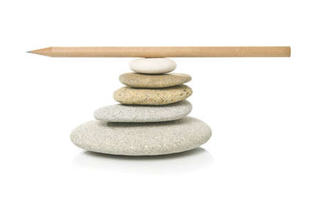 Stock photo of a stack of pebbles with a pencil balanced on top. Stock Photo