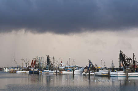 Fishing trawlers moored in harbour during an afternoon storm.