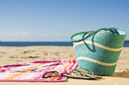 sandalia: Toalla vibrante, bolsa de playa y accesorios esparcida en la arena.