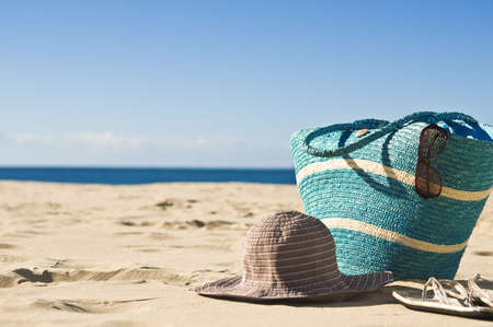 A view of the beach. Focus on the foreground,with bag, hat, sunglasses and sandals.