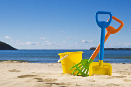 A beautiful day at the beach. Focus on rack,spade and bucket.