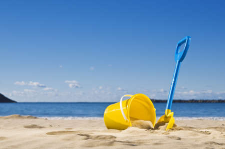waters: Spade and bucket by the waters edge, ready to build a sandcastle. Stock Photo