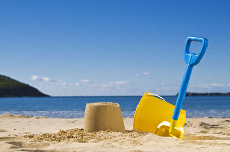 Shot of the beach on a sunny day, with a spade and bucket in foreground.