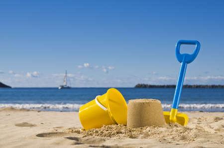 emmer water: Schot van het strand met een spade en emmer op voorgrond.