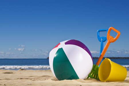 Day at the beach with a beach ball, spade and bucket in the foreground.  Stock Photo