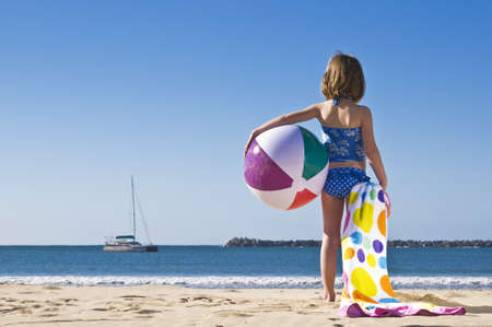 Young child standing with beachball and towel ready to play.