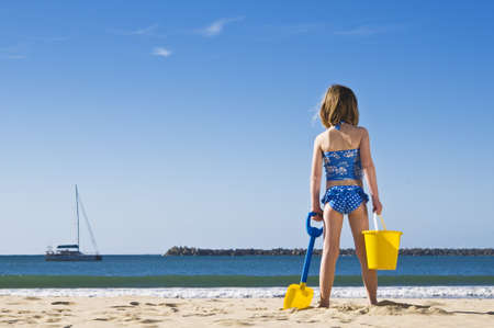 Young child at the water's edge ready to play in the sand, with spade and bucket.