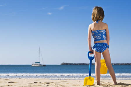 Young child with spade and bucket standing on the beach. Stock Photo