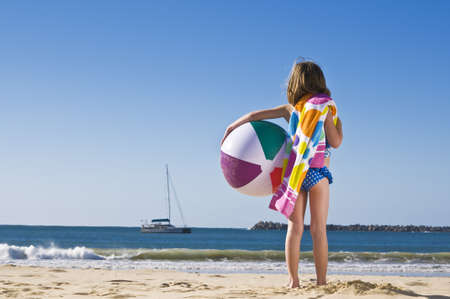 Young child holding towel and beach ball at the beach. Stock Photo