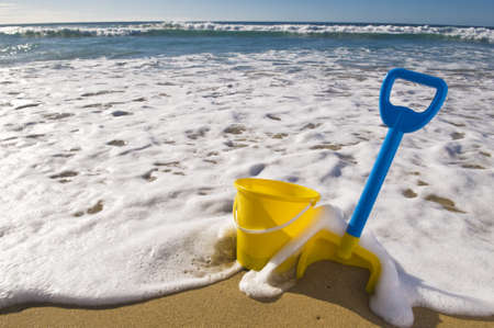 tides: Beach scene, Spade and bucket at the waters edge.