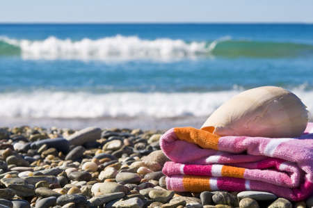 Close up of a towel and shell on a beach.