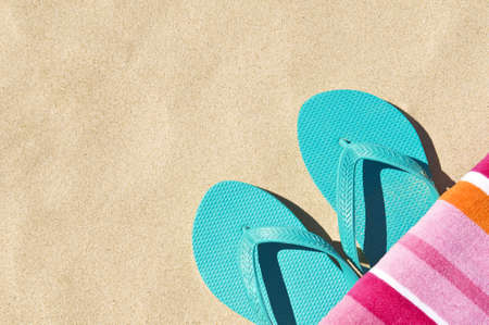 Location shot of a brightly coloured towel and a pair of thongs/flip-flops.