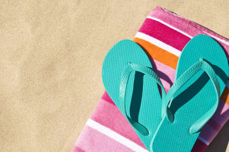 Flip-flops/Thongs and towel on white sand.