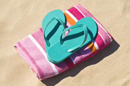 Location shot of a pair of flip-flops/thongs on a towel at the beach.