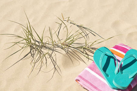 Towel flip-flops/thongs on the sand with beach grass.