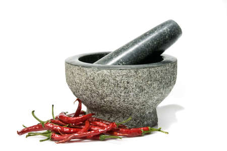 Fresh red chillies with pestle and mortar, isolated on a white background. Stock Photo