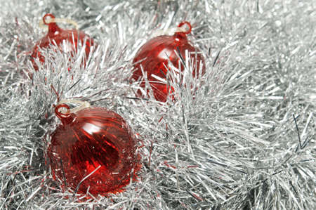 Three red glass baubles on a bed of silver tinsel.