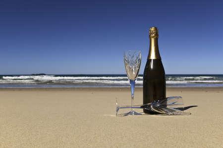 boda en la playa: Botella de champagne con dos copas de cristales en una playa solitaria