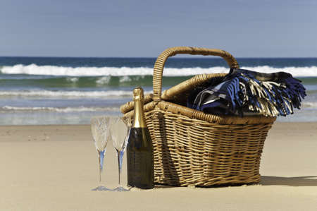Champagne,glasses,picnic basket and blanket,perfect for a afternoon at the beach  photo