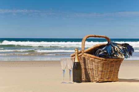 anniversary beach: Champagne,glasses,picnic basket and blanket,perfect way to celebrate. Stock Photo