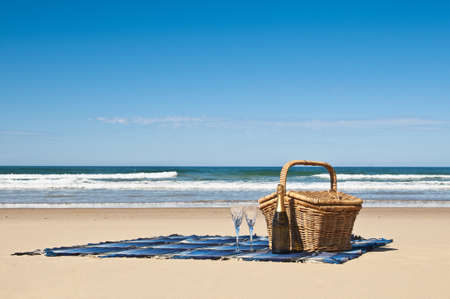 Picnic blanket,champagne,picnic basket and a beautiful tropical beach  Stock Photo