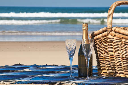anniversary beach: Picnic blanket,champagne,picnic basket and a beautiful tropical beach  Stock Photo