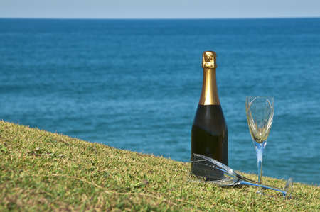 Champagne and glasses on the top of a headland overlooking the ocean