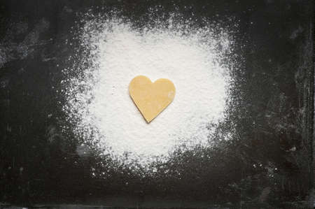 Shortbread love heart biscuit on flour and baking tray