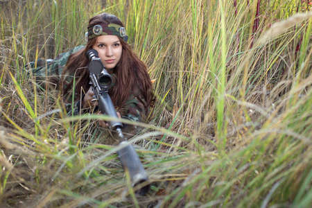 Young girl with a rifle peeking out of the grass Reklamní fotografie