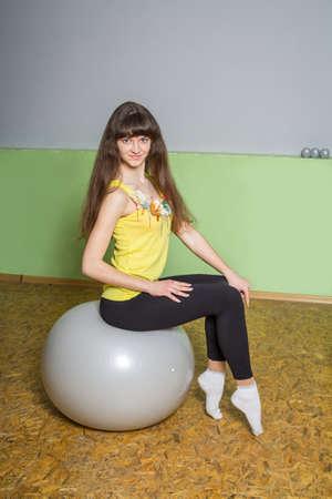 Mädchen mit langen Haaren machen Übungen in der Turnhalle