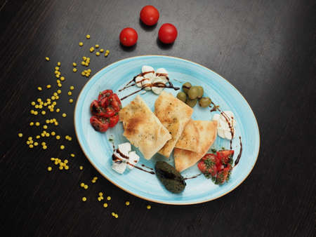 Snack on a plate of cheese, tomatoes, olives and pita on a dark table